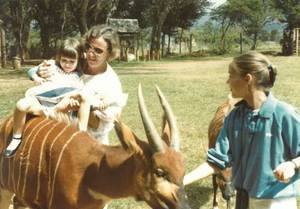 During the 1980s in Kenya: little Daniella (left) climbs onto a bongo antelope, helped by her mother Marliese, while sister Denise watches.