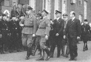 Nazi officials march past the Seitz-Werke workforce assembled in rank and file for the occasion.