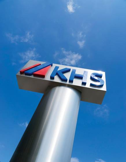 "The three letters ""KHS"" stand for Klöckner, Holstein and Seitz and together with the stylized red and blue stripes form the merger logo."