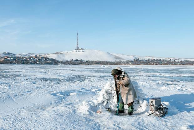 On frozen Lake Kopa, a Kazakh fisherman drills a hole in the hope of making a good catch in the meter-thick ice. The mountain slope in the background sports the name of the town Hollywood-style in the winter sun.